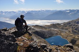 Chugach State Park - A hiker on the summit of Gentoo Peak, with upper Turnagain Arm in the background. Turnagain Arm is a largely silt-clogged fjord known for its extreme tides (including bore tides), treacherous silt flats, and population of beluga whales.