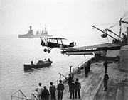 A small biplane has just taken off from a warship, having used a platform built over the roof and barrels of a twin-barrelled turret. Sailors are observing the launch from the deck of the ship, and from a small boat nearby. A large warship is visible in the background.