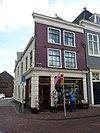 foto van Pand met lijstgevel, beneden winkelpui uit later tijd, gevel met rechte daklijst, diep doorlopend in donkere begijnhof