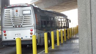 Silver Line (Los Angeles Metro) - Metro Silver Line bus at Harbor Freeway station showing yellow bollards installed after a private vehicle drove onto the platform injuring waiting passengers.