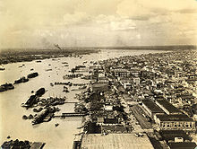 A sepia tone aerial photograph of Calcutta showing the Hooghly river and buildings.
