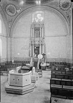 A sepia photograph shows the interior of the synagogue. In the foreground lies the reading desk atop a simply paneled almemar. Rows of wooden benches line the right and left side of the nave. The holy ark, set in the centre of the eastern wall, is decorated with baroque carvings and set off against four Corinthian columns. Its top reaches a large clover-shaped window, which sits just below one of the four supporting arches. The walls faintly show decorative murals, with two large round frescos situated at the top left and right corners.