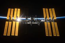 Am image of the International Space Station. The silver-colored center module is dark blue, surrounded by four golden solar arrays on each side. The sun is reflecting off of the set to the left. In the background is the outline of the Earth.