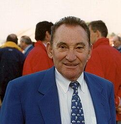 Photographie d'un homme porteur d'une chemise blanche et d'une veste bleue