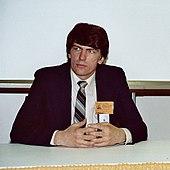 photographie couleur d'un homme assis derrière une table
