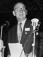 Man in suit speaks at a microphone