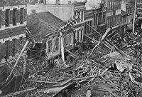 Černobílá fotografie řady budov s rozbitým dřevem vpředu