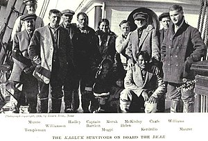 Ten men, one woman and two children stand (one man crouching) on a ship's deck. Both children are largely obscured in shadow. They are warmly dressed, mostly in thick jackets and boots, and the facial expressions of most are sombre and weary, although a few are attempting to smile.