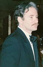 Photo of a man who has a thin mustache dressed in a black suit, white collared shirt, and black bowtie.