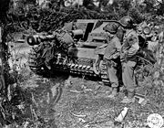 US troops of the Third Armored Division examine a knocked out German Sturmgeschutz III with a dead German crewman on the gun barrel.
