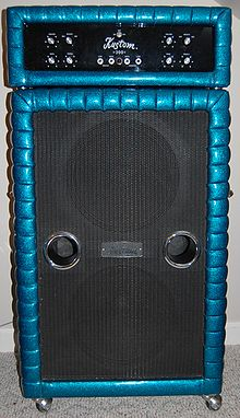 A 1970s era amplifier unit sitting on top of a large bass speaker cabinet. The speaker cabinet contains two fifteen-inch loudspeakers.