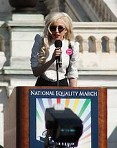 A blond woman wearing a white shirt and black glasses speaking on a lectern carrying a 'National Equality March' poster. Behind her is a white stone balustrade of a building.