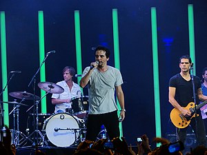 Wagner Moura - Surviving members of Legião Urbana performing a 2012 tribute show with Moura as lead vocalist. From left to right: Marcelo Bonfá, Moura and Dado Villa-Lobos. To their right and partially cut out of the picture is touring bassist Rodrigo Favaro