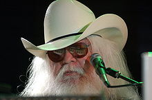 Musician Leon Russell is shown from the head up in front of a microphone.