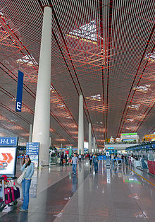 A view down a long vista on the inside of an airport terminal building. Tot the right are check-in stations; to the left a long row of tall white round smooth pillars go up to the ceiling, where triangular windows let sunlight in. The sunlight is reddish from the surrounding superstructure, but filtered through white strips below.