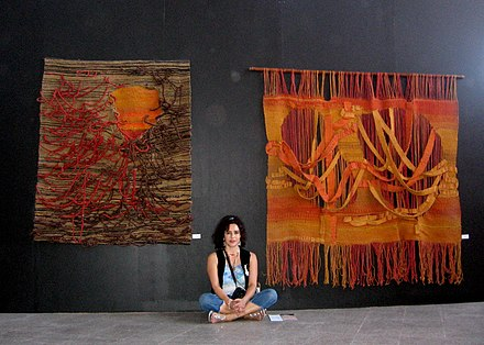 Lorena Lemunguier Quezada (Mapuche) with two of her weavings at the Bienal de Arte Indigena, Santiago, Chile. Lorena Lemunguier Quezada junto a sus obras.jpg