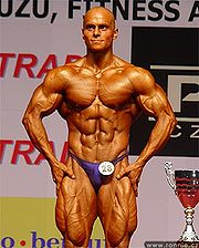 A bodybuilder posing on stage during competition