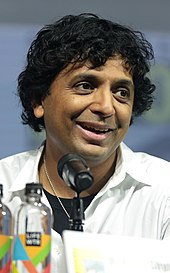 M. Night Shyamalan at a San Diego Comic-Con panel wearing a white shirt and talking into a microphone.