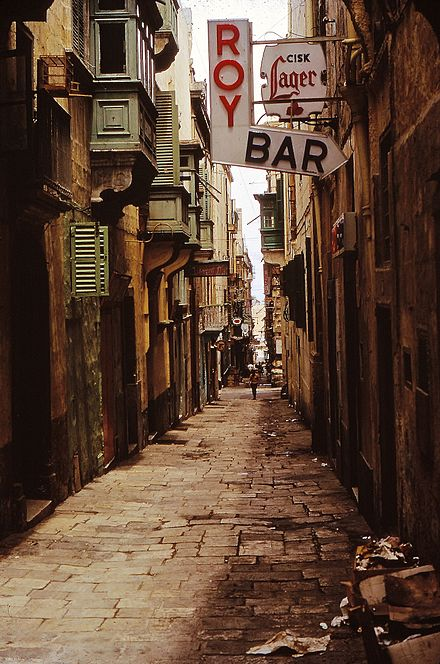 "Early morning in 1967 on the notorious Straight Street known to generations of British Servicemen (especially to sailors on shore leave) as ""The Gut"". Bars and bordellos abounded, and brawls were common. But its popularity never waned. Malta GC. Valletta-1967 (8240967236).jpg"