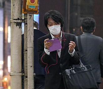 Surgical mask - A man wearing a surgical mask in public in Japan.