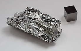 Molybdenum crystaline fragment and 1cm3 cube.jpg
