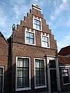 foto van Huis met trapgevel, bekroond door een fronton en voorzien van gebeeldhouwde kopjes in de strekken der vensters
