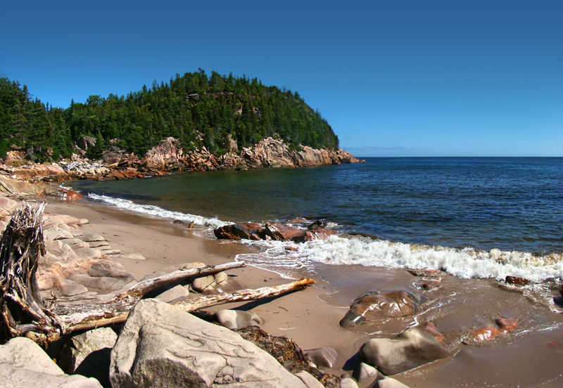 a rocky beach with a cape and blue skies in the background, in the Cape Breton Highlands region