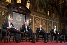 Four men in suits sit on chairs on a red stage in front of an ornate gold and brown wall.