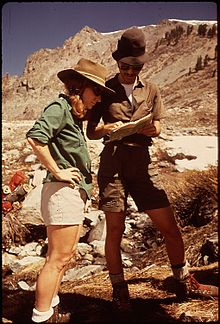 Photograph of a man and woman in the Sierra Nevada mountains looking at a book.