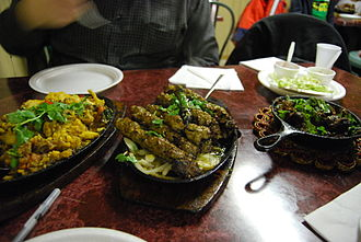 Pakistani cuisine - A variety of Pakistani dinner dishes – Starting from the left: gobi aloo, seekh kebab, and beef karahi