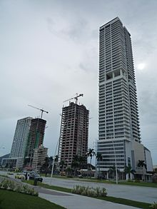 Two tall buildings, with construction cranes on top, next to much taller skyscraper