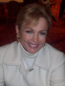 Portrait photo of a woman with blonde hair in her late 50s smiling at the camera. She is wearing a white coat and white turtleneck underneath.