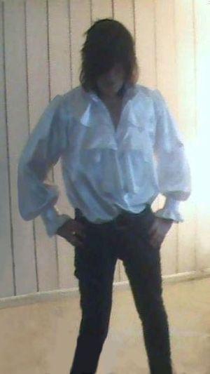 Poet shirt - A man wearing a ruffled white satin poet shirt.