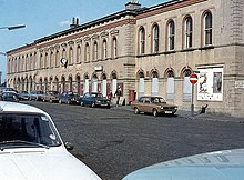 A white neo-Victorian station building, with a street full of parked 1970s cars in front of it.