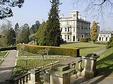 Un escalier de pierre menant à un petit jardin à la française en contrebas sur la gauche. Au loin sur la droite, derrière quelques arbres, se trouve un grand bâtiment cubique en pierres blanches, ressemblant à un manoir, avec de nombreuses cheminées et fenêtres