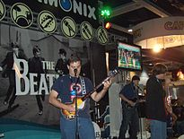 A color photograph of three young men playing on the The Bealtes: Rock Band instruments in front of a large display for the game.