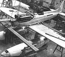 A single-engined floatplane is being built in a hangar, the engine covers are removed.