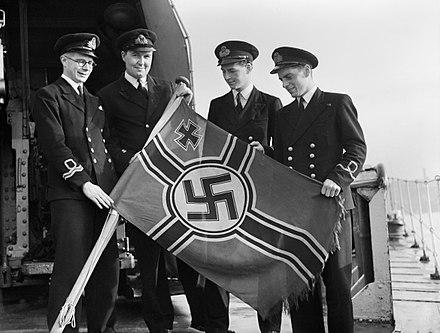 Royal Navy officers aboard HMS Garth with a captured German E-boat ensign at Sheerness, 21 October 1944. (IWM) A26034 Royal Navy officers aboard the destroyer HMS GARTH with a captured German E-boat ensign at Sheerness, 21 October 1944. A26034.jpg