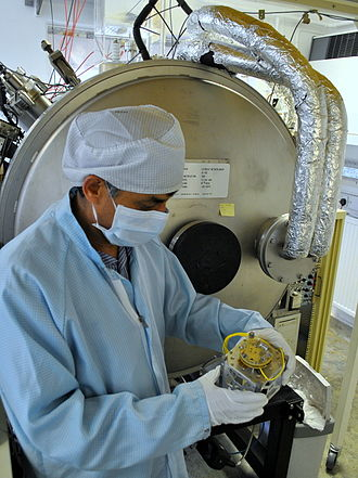 Mullard Space Science Laboratory - Scientist holding a CubeSat in front of MSSL's thermal vacuum facility
