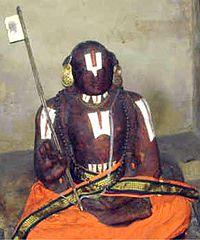 An idol made of black stone dressed in orange robes, with a flag in a hand and Thirunamam on the forehead, throat, chest and hands.