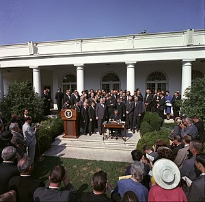 War on Poverty - President Lyndon B. Johnson signs the Poverty Bill (also known as the Economic Opportunity Act) while press and supporters of the bill look on, August 20, 1964
