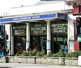 "Station entrance with portico and ornamental ironwork signage above stating ""Metropolitan and District Railways"", ""South Kensington station""."