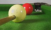 Une vue rapprochée d'une balle blanche grêlée à l'avant et à gauche d'une balle de billard rouge qui est elle-même à côté d'une poche d'angle dans le coin supérieur droit de l'image.  La pointe d'un bâton de repère est visible dans le coin inférieur droit de l'image, sur le point de frapper la boule blanche.