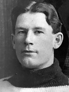 Cropped image of the head of a man in his early 20s, wearing a wool sweater, staring just past the camera
