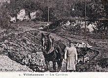Photo d'un homme dirigeant un cheval qui tracte une charge sur un chemin de fer.