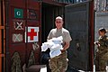 U.S. Air Force Senior Master Sgt. Eric Harriff, left, with Combined Joint Interagency Task Force 435, carries clothing donations to be repackaged for an Operation Outreach Afghanistan program at Camp Phoenix 130728-D-BO405-040.jpg