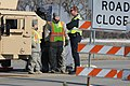U.S. Army Pfc. Summer Kristianson, left, and Sgt. Shannon Welsh, center, both with the 191st Military Police Company, North Dakota Army National Guard, talk with a police officer while directing traffic during 130423-Z-WA217-009.jpg