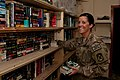 U.S. Army Sgt. Jenna Moffitt, a truck commander assigned to the 110th Transportation Company, 419th Combat Sustainment Support Battalion, 10th Sustainment Brigade, places books on a shelf at the American Red 140901-A-CA521-015.jpg