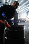 U.S. Navy Electrician's Mate 2nd Class Brandon Osefoh fills a drum with water during a damage control olympics competition June 10, 2013, aboard the aircraft carrier USS George H.W. Bush (CVN 77) in the Atlantic 130610-N-XE109-098.jpg