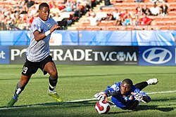 Austrian forward Rubin Okotie tries to shoot past Congo goalkeeper Destin Onka at the 2007 FIFA U-20 World Cup. Onka makes the save. (shot at Commonwealth Stadium in Edmonton, Alberta, Canada)